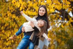 有她的小女儿的年轻美丽的母亲在秋天公园 库存图片