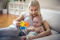 有她的小男婴的年轻母亲在家 免版税库存图片