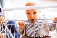有她的小男婴的年轻母亲超级市场的 免版税库存照片
