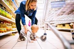 有她的小男婴的年轻母亲超级市场的 免版税库存图片
