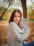 有她的小男孩的年轻母亲,在秋天公园 库存图片