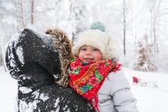 有她的小逗人喜爱的女儿的一名年轻美丽的妇女在冬天公园 特写镜头 免版税图库摄影