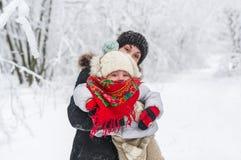 有她的小逗人喜爱的女儿的一名年轻美丽的妇女在冬天公园 库存照片