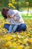 有她的小婴孩的愉快的年轻母亲在秋天公园 库存图片