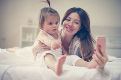 有她的小婴孩的母亲获得乐趣在床 免版税库存图片