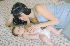 有她的小婴孩的爱恋的母亲在床上 免版税图库摄影