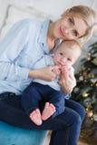 有她的年轻儿子的愉快的母亲在圣诞树附近的圣诞前夕 免版税库存照片