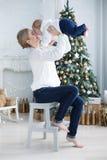 有她的年轻儿子的愉快的母亲在圣诞树附近的圣诞前夕 图库摄影