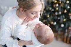 有她的年轻儿子的愉快的母亲在圣诞树附近的圣诞前夕 库存图片