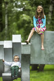 有她的弟弟的女孩操场的在城市公园 免版税库存照片