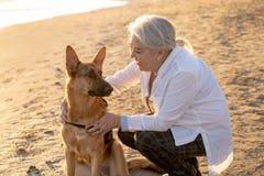 有她的德国shepard狗的画象o愉快的可爱的资深妇女在秋天日落的海滩 库存照片