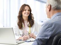 有她的患者的女性医生 免版税库存照片