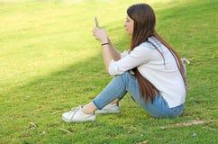 有她的手机的青少年的女孩 库存图片