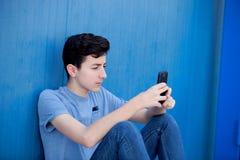 有她的手机的年轻少年 库存照片