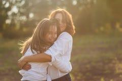 有她的拥抱一个少年的女儿的愉快的母亲在夏天 免版税库存照片