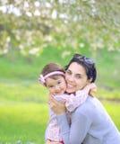 有她的拥抱在公园的孩子的母亲 免版税库存照片