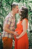 有她的握在她的腹部的丈夫的年轻人孕妇手 免版税库存图片