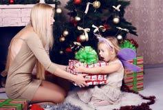 有她的摆在圣诞树和礼物旁边的妈妈的滑稽的小女孩 免版税库存图片