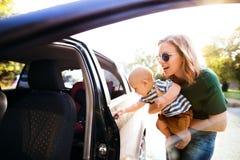 有她的支持汽车的小男婴的年轻母亲 库存照片