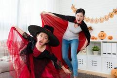 有她的母亲佩带的吸血鬼斗篷的女孩佩带的巫婆礼服 库存图片