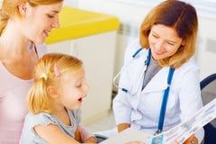 有她的母亲参观的医生的孩子 免版税库存图片