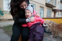 有她的母亲和一条蓬松狗的小和甜女孩 库存照片
