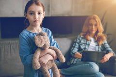 有她的母亲忽略的玩具的孤独的女孩 图库摄影