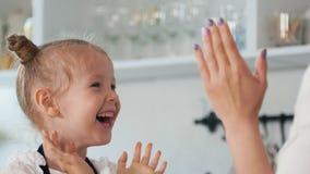 有她的母亲拍手的愉快的小女孩他们的手在厨房里 图库摄影