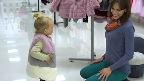 有她的母亲的一个小甜女孩选择儿童在精品店的` s衣裳 妈妈和孩子在商店选择衣裳 影视素材