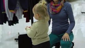 有她的母亲的一个小甜女孩选择儿童在精品店的` s衣裳 妈妈和孩子在商店选择衣裳 股票录像