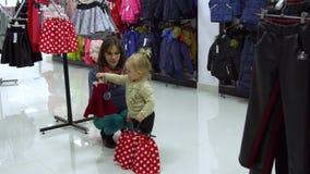 有她的母亲的一个小甜女孩选择儿童在精品店的` s衣裳 妈妈和孩子在商店选择衣裳 股票视频