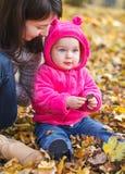 有她的母亲的可爱的女婴 免版税库存图片