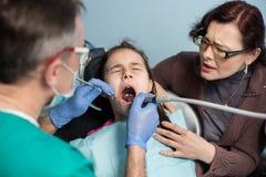 有她的母亲的女孩第一次牙齿参观的 做患者的牙齿做法资深男性牙医 免版税库存照片
