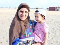 有她的母亲的愉快的微笑的阿拉伯回教女婴 免版税库存图片