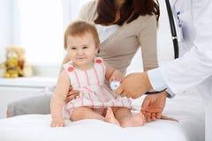 有她的母亲的愉快的逗人喜爱的婴孩健康检查的在医生` s办公室 库存图片