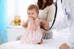 有她的母亲的愉快的逗人喜爱的婴孩健康检查的在医生` s办公室 免版税库存图片
