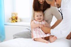 有她的母亲的愉快的逗人喜爱的婴孩健康检查的在医生` s办公室 库存照片