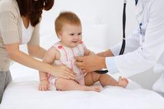 有她的母亲的愉快的逗人喜爱的婴孩健康检查的在医生` s办公室 免版税图库摄影