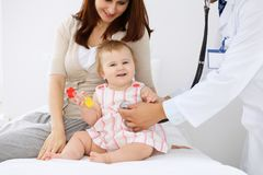 有她的母亲的愉快的逗人喜爱的婴孩健康检查的在医生` s办公室 图库摄影