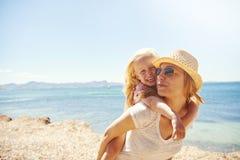 有她的母亲的笑的小女孩海滩的 库存照片
