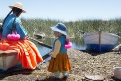 有她的母亲的艾马拉女孩在其中一个的shoreside的Uros海岛 图库摄影