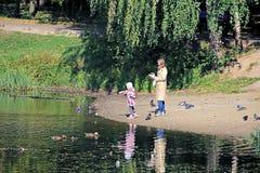 有她的母亲饲料鸟的女孩在池塘 免版税库存照片