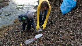 有她的清扫垃圾的孩子的妇女志愿者由河 生态和环境概念 股票录像