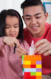 有她的演奏玩具块的兄弟的女孩 免版税库存照片