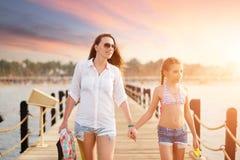 有她的漫步沿码头的女儿的少妇 库存照片