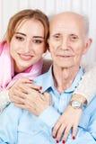 有她的照料者的老人在家 库存照片