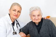 有她的照料者的老妇人 免版税库存图片