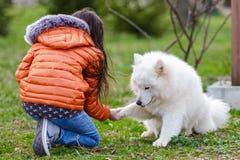 有她的爱犬的一个小美丽的女孩 免版税图库摄影