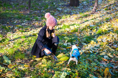 有她的爱犬outdooors的小白肤金发的女孩在公园 免版税库存图片