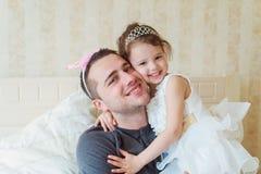 有她的父亲佩带的冠的逗人喜爱的小女孩 库存照片
